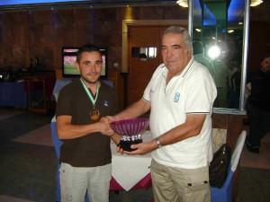 Ángel Fernández recibe el trofeo de campeón de manos de Julio Martín, presidente del Comité de Salmónidos.